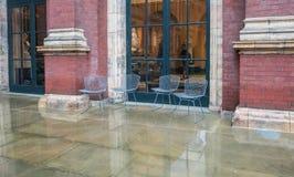 Leere Gartenstühle in regnerischem Victoria- und Albert Museum-Hof, Stockbild