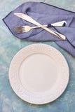Leere Gedeckanordnung, weiße Platte, Tischbesteck, blaue Serviette, konkrete Tischplatte, flatlay Lizenzfreie Stockbilder