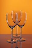 Leere Gläser auf Orange Stockfotos