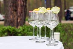 Leere Gläser mit Scheiben des Kalkes und der Zitrone, verzierter Zucker, der die Tabelle bereitsteht Stockbilder