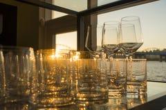 Leere Gläser Whisky und Wein bei Sonnenuntergang auf Innentabelle mit Flussansichtfenstern stockbilder