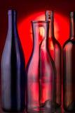Leere Glasflaschen auf rotem Hintergrund Stockfotografie