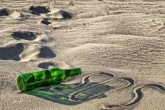Leere grüne Flasche auf dem Sand Stockbild