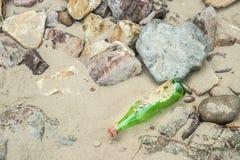 Leere grüne Flasche auf dem Sand Lizenzfreies Stockbild