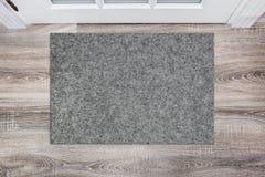 Leere graue woolen Fußmatte vor der weißen Tür in der Halle Matte auf Bretterboden, Produkt Modell lizenzfreie stockfotos