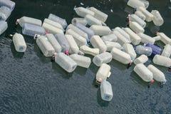 Leere große Plastikbehälter, Wasserkanister, die in eine Bucht im Atlantik schwimmen lizenzfreies stockfoto