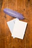 Leere Gruß-oder Einladungs-Karte mit Umschlag und purpurroter Feder Stockfotos