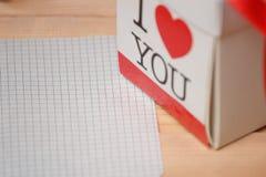 Leere Grußkarte und -Geschenkbox über Holztischhintergrund Stockbilder