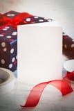Leere Grußweißkarte Eingewickeltes Geschenk und Verpackungsmaterial über einem weißen hölzernen Hintergrund Abbildung der roten L Stockbilder