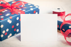 Leere Grußweißkarte Eingewickeltes Geschenk und Verpackungsmaterial über einem weißen hölzernen Hintergrund Abbildung der roten L Stockfoto