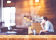 Leere hölzerne Tabelle mit Unschärfekaffeestubehintergrund, verspotten herauf Templa stockfotos
