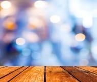 Leere hölzerne Tabelle und Kaffeestube verwischen Hintergrund mit bokeh imag Lizenzfreie Stockfotos