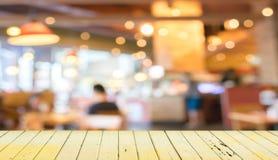 Leere hölzerne Tabelle und unscharfer Kaffeestubehintergrund lizenzfreie stockfotografie
