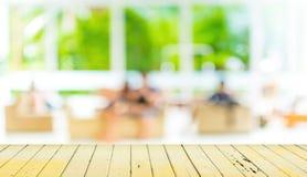 Leere hölzerne Tabelle und unscharfer Wohnzimmerhintergrund Stockfotos