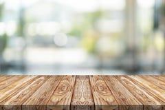 Leere hölzerne Tischplatte auf grünem Unschärfehintergrund am Einkaufszentrum stockfoto