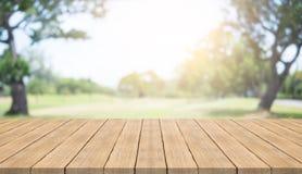 Leere hölzerne Tischplatte auf Naturgrün verwischte Hintergrund lizenzfreie stockfotos