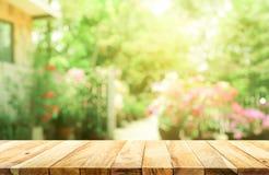 Leere hölzerne Tischplatte auf Unschärfezusammenfassungsgrün vom Garten stockfotografie