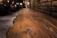 Leere hölzerne Tischplatte der Bar mit Unschärfe des Caférestaurants in der Dunkelheit Stockbilder