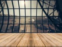Leere hölzerne Tischplatte mit Flughafenabfahrtzusammenfassungs-Unschärfehintergrund mit bokeh Licht lizenzfreie stockfotografie