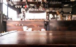Leere hölzerne Tischplatte mit Unschärfe der abstrakten Kaffeestube oder des Cafés Stockfotografie