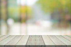 Leere h?lzerne Tischplatte auf gr?nem Unsch?rfehintergrund am Einkaufszentrum lizenzfreies stockfoto