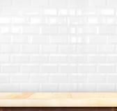 Leere helle hölzerne Tabelle und weiße Rückseite der Keramikziegelbacksteinmauer herein Lizenzfreie Stockfotografie