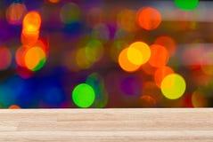 Leere helle hölzerne Tischplatte mit buntem Hintergrund Für neues Jahr, können Weihnachten oder jedes mögliches Feiertagsereignis Lizenzfreies Stockbild