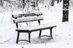 Leere Holzbank im Park im Winter wird mit Schnee bedeckt Stockbilder