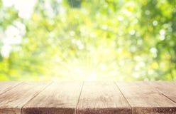 Leere Holztisch-Planken über Grün unscharfem Baum-Hintergrund Stockfoto