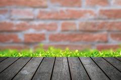 Leere Holztischplattform mit Backsteinmauerhintergrund stockfotos