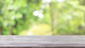 Leere Holztischschablone auf die Oberseite mit dem Naturgrünhintergrund, der mit windigem über beeinflussenden Bäumen für Montage stock footage