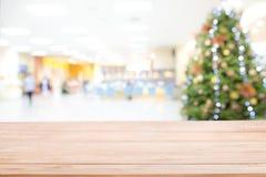 Leere Holztischspitze über unscharfer Zusammenfassung des verzierten Weihnachtsbaums mit Spielwaren, Geschenkbox und Flitter inne lizenzfreies stockbild