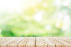 Leere Holztischspitze mit unscharfem grünem Gartenhintergrund stockbild