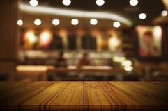 Leere Holztischspitze mit unscharfem hellem BAC des Restaurants oder des Cafés Lizenzfreies Stockbild