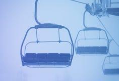 Leere Kabinen des Sesselliftes auf Drahtseilbahn im starken Nebel Lizenzfreie Stockfotos