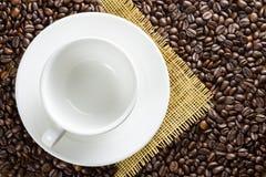 Leere Kaffeetasse mit Untertasse auf Kaffeebohnehintergrund Lizenzfreie Stockbilder