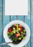 Leere Karte auf blauem hölzernem Schreibtisch mit Lebensmittel Stockfotografie