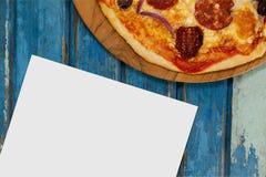 Leere Karte auf blauem hölzernem Schreibtisch mit Lebensmittel Stockfotos