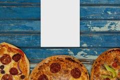 Leere Karte auf blauem hölzernem Schreibtisch mit Lebensmittel Lizenzfreie Stockfotos