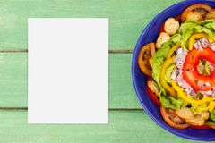Leere Karte auf grünem hölzernem Schreibtisch mit Lebensmittel Lizenzfreies Stockbild