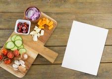 Leere Karte auf hölzernem Schreibtisch mit Lebensmittel Lizenzfreies Stockfoto