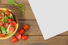 Leere Karte auf hölzernem Schreibtisch mit Lebensmittel Lizenzfreie Stockfotos