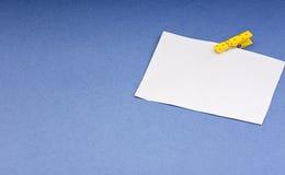 Leere Karte mit Raum für Anmerkungen über das farbige Papier der hölzernen Wäscheklammer auf blauem Hintergrund Stockbild