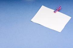 Leere Karte mit Raum für Anmerkungen über das farbige Papier der hölzernen Wäscheklammer auf blauem Hintergrund Lizenzfreie Stockfotografie