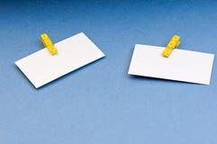 Leere Karte mit Raum für Anmerkungen über das farbige Papier der hölzernen Wäscheklammer auf blauem Hintergrund Stockfotos