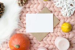Leere Karte mit Umschlag auf Merinowollewurfs-Deckenhintergrund Modellschablonen-Ebenenlage Ansicht von oben Lizenzfreies Stockfoto