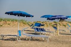 Leere Klappstühle unter Regenschirmen auf Strand stockbild