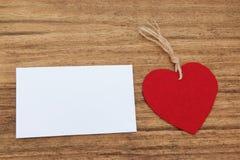Leere klebrige Anmerkung mit einem roten Herzen auf einem hölzernen Hintergrund Stockbilder