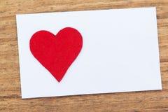 Leere klebrige Anmerkung mit einem roten Herzen auf einem hölzernen Hintergrund Lizenzfreie Stockfotografie
