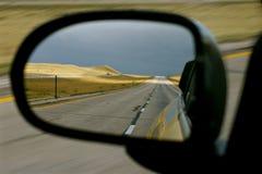Leere Land-Straße im Seitenansicht-Spiegel Stockfotos